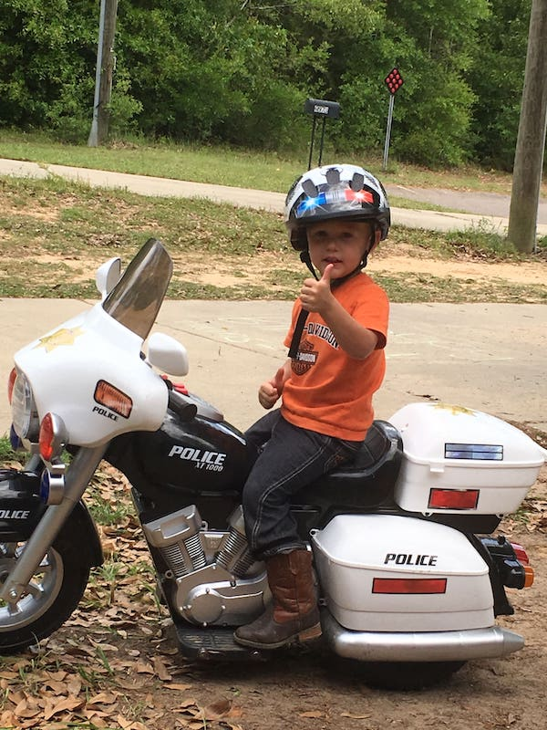 Aiden Hensley gives a thumbs up on his black and white mini Harley Davidson in Mobile, Alabama.