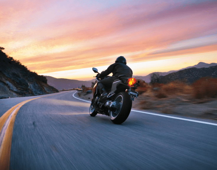 riding motorcycle into sunset
