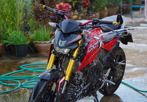 motorcycle being sprayed with hose.